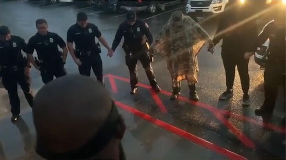 Jon Jones cầu nguyện cùng cảnh sát. Ảnh chụp màn hình.